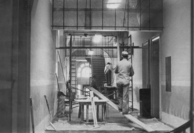 Administration Building interior; first floor hall  and lobby area, workmen doing renovation work