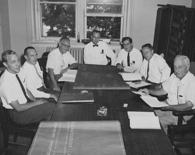 Seven unidentified men sitting around table reviewing blueprints and building plans marked