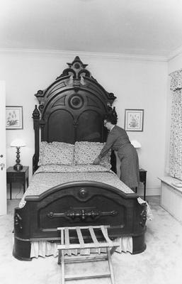 Unidentified woman making a bed in the Carnahan House
