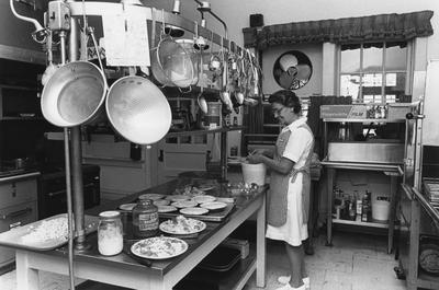 Unidentified woman preparing food in the Carnahan House kitchen