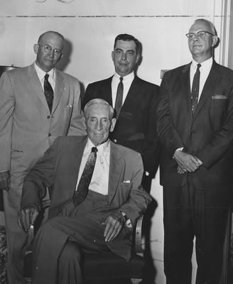 Frank D. Peterson (standing, left) two unidentified men (standing, center and right) and James W. Carnahan (seated) pose for a picture at reception for Carnahan House dedication