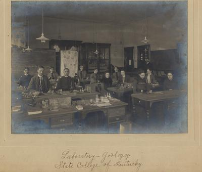 A zoology laboratory with Professor M. Miller standing by the door. This building is now Miller Hall. W. P. Johnson class of 1901 is the first person in the front row on the left side