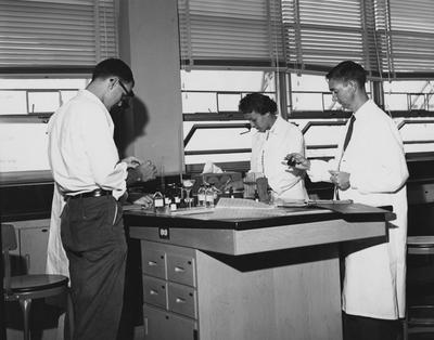 Four unidentified people are performing an experiment. This photo received December 30, 1959 from Public Relations