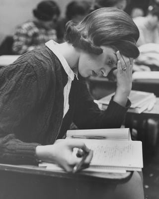 An unidentified female student is taking note in class