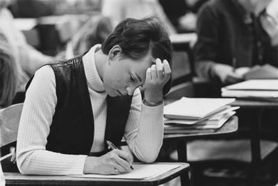 An unidentified female student is taking a final exam. This photograph appears first on page 133 in the 1969