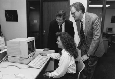 Mark Denomme (standing to the right) and two unidentified people gather around a computer in the computer lab for this photograph