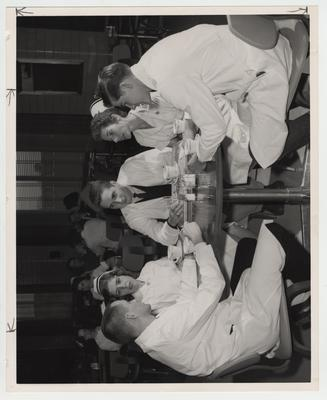 Men and women sit at a table in a dining room of the Medical Center