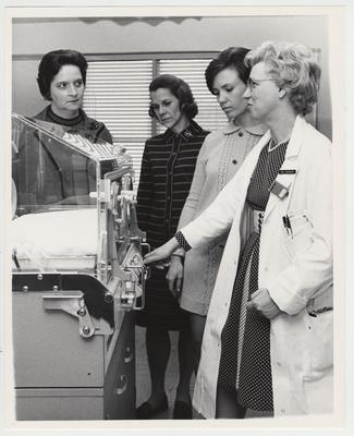 Dr. J. Noonan and three unidentified women look at the neonatal unit