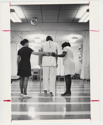 Nurses helping a man walking with a walker