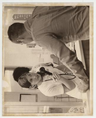 A female nurse, telephone in hand, helps an unidentified man