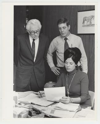 Two men read a paper over the shoulder of a woman sitting at a desk