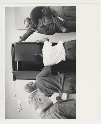 Four African - American men and another man unload a cabinet