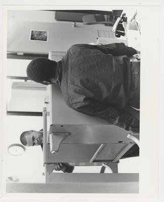 An African - American man and another man carry a desk