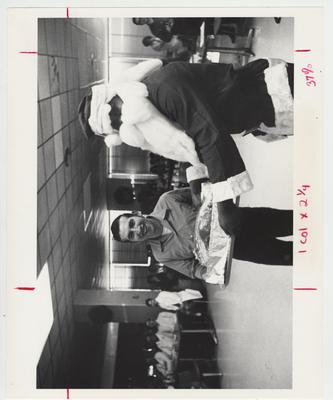 Charles McCarty carries a turkey at the Christmas party in the Medical Center