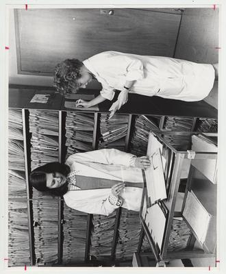 Two women going through files