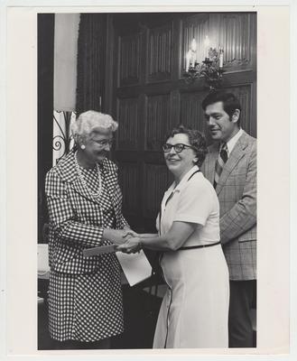 Two unidentified women shake hands as an unidentified man looks on