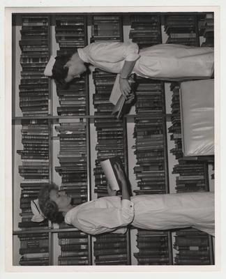 Two female nurses look at books in a library