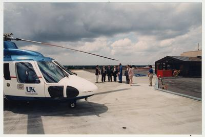A group of men and women stand on a helicopter pad (located on the top of the Chandler Medical Center) listening to an unidentified man