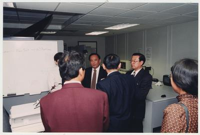 Visitors from Shandong University Medical School in Shandong Ji ' Den, China listening to an unidentified man in the Medical Center