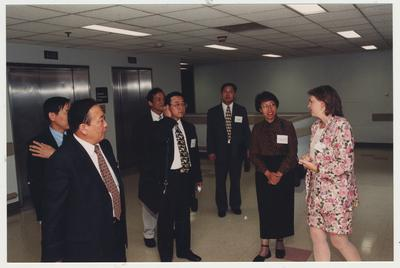 Visitors from Shandong University Medical School in Shandong Ji ' Den, China taking a tour of the Medical Center with an unidentified woman