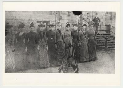 Women identified as the Broom Brigade drilled with brooms as the men did with guns.  From left to right: 1. unidentified, 2. Minnie Moore (later a retired school teacher), 3. Mrs. Ernest Cassity (her sister), 4. Sally Belle Baker, 5. Mayme Combs, 6. Elmer Allen, &. Kate Baker, 8. Hattie Warner, 9. Annie Baker, 10. Sallie Hornbrook.  On the steps: 1. Mary Lou Baker, 2. Vergie Hearne, 3. Joe Hearne