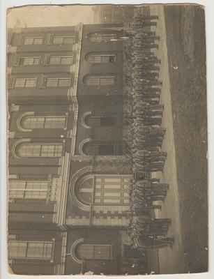 Company of cadets in uniform with rifles in front of the Administration Building