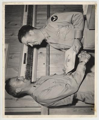 Two men shaking hands and Roger S. Tennant receiving a certificate at the Headquarters of the Army Air Force Bombardier School in Big Spring, Texas