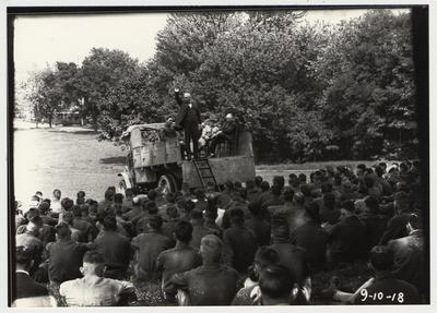 University of Kentucky military training during World War I.  A man giving a speech to several cadets.  F. Paul Anderson is seated in a chair in the back of the truck