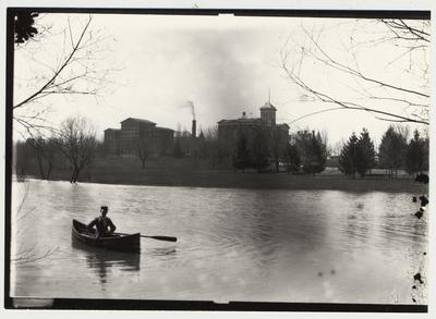 University of Kentucky military training during World War I.  A man in a canoe on the lake near the Administration building