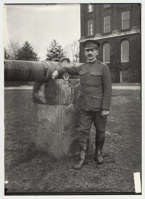 University of Kentucky military training during World War I.  Military officer standing next to a cannon