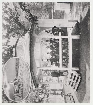 Scene of encampment of State College cadets near Ashland, Kentucky.  10 men with instruments posing on a gazebo.  Inset picture of a man on a wagon