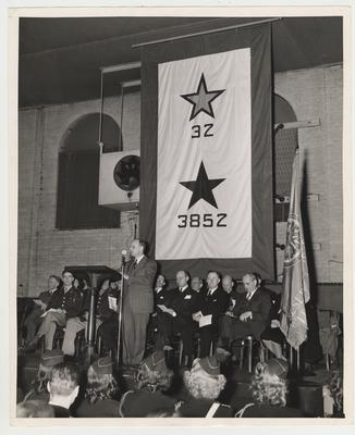This print is dated circa 1946-1947 during President Donovan's term of office (1946-1956).  It depicts a ceremony held in the Alumni Gym honoring veterans after World War II