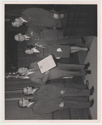 From left to right: Cadet Major Robert Crosson, Cadet Lieutenant Colonel Joseph Jones, Governor Edward T. Breathitt, Judy Gooch, Lieutenant Colonel John Delap, and Captain W. H. Franklin.  Governor Breathitt is awarded the Honorary Cadet Colonel