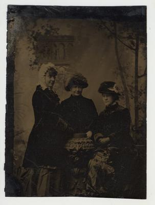 Three women dressed nicely posing for a picture.  Tintype