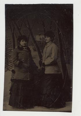 Two women dressed nicely posing for a picture.  Tintype