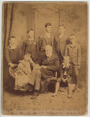 Standing from the left: Sebastian, 13; Edward, 15; Hervey, Jr., 18; Marshall, 17; Marion, 14.  Sitting from the left: Anna Mary, 10 1/2; Alex K. M. McDowell, 83; Jo Desha, 6.  A message on the back reads:
