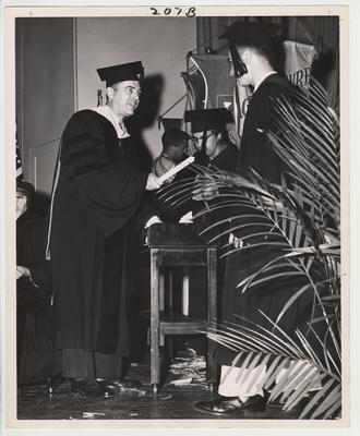President Frank Dickey (left) in cap and gown presenting a diploma to an unidentified male graduate.  This photo is in the 1957 Kentuckian on page 207, picture number 7