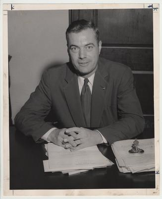 President Frank Dickey seated at his desk with his hands folded