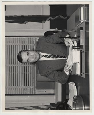 President Frank Dickey seated at his desk, holding a pen and document