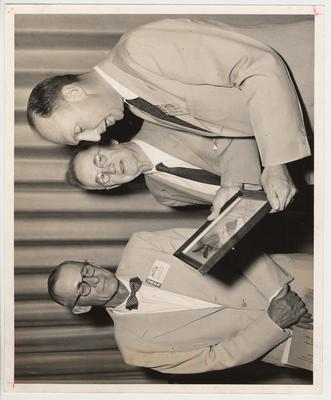 H. K. Gayle of Lexington, Kentucky (left) and Laban Jackson (far right) are giving President Donovan (center) an award.  H. K. Gayle and Laban Jackson are part of the United States Department of Agriculture
