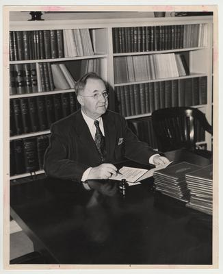 President Donovan seated at a table in a library signing diplomas