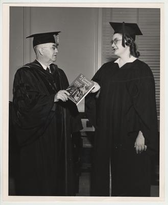 President Donovan hands the 14,000th recipient of a diploma a copy of the James F. Hopkins book The University of Kentucky: Origins and Early Years