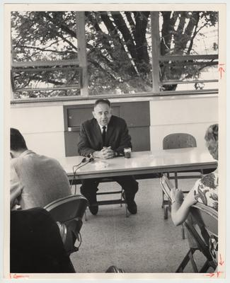 President John Oswald is seated at a table near open windows and speaking into microphones for an interview in the Student Center