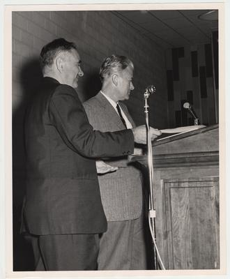 President John Oswald (left) and Governor Bert Combs standing at a podium