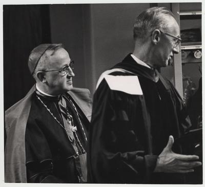 An unidentified Catholic Bishop and an unidentified man prepare for president Oswald's inauguration ceremony