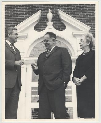 Richard Cooper (far left) handing President John Oswald (center) a check from an unknown donor as Helen King (far right) watches