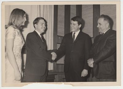 Three unidentified students, two men and one woman, are in the administration office with President Oswald (far right)