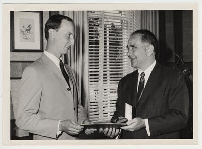 President Oswald presenting a Hamilton watch award to an unidentified student for an academic award