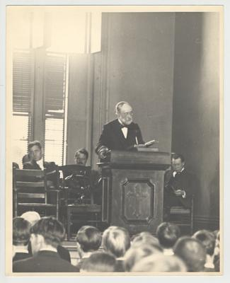 President James K. Patterson speaking on a chapel platform with unidentified people sitting behind him