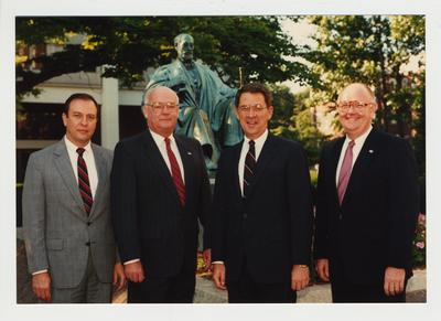 President Roselle (second from the right) and three unidentified men standing in from of the James Patterson statue in front of the Administration building and near the Patterson Office tower